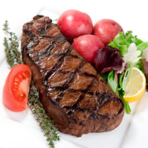 A hearty thick cut New York Strip steak grilled to Medium Rare and served with a side salad and steamed red potatoes.  Shallow dof