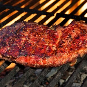 Single Great BBQ Pepper Beef  Steak On The Hot Flaming Grill Close-up. Good Food For Outdoor Summer Barbecue Party Or Picnic
